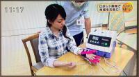 七沢リハビリテーション病院脳血管センターでリポーターの小村弥生さんがパワーアシストハンドを試している写真