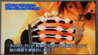 若大将(加山雄三)がパワーアシストハンドを使用しながら「手の甲に付いた蛇腹が空気圧で伸縮することで指の関節を継続的に動かす」と紹介されている写真